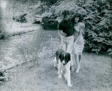 Horst Werner Buchholz walking with his wife and a dog in the garden. 1961