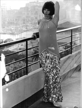 Leslie Caron standing on balcony