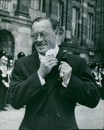 Prince Bernhard of the Netherlands smiling while fixing his suit.