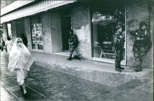Soldiers standing in front of a store with Muslim woman passing by, during the war in Algeria, 1962.