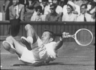 Rod Laver falls on the tennis court