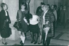 An unconscious woman being led by other women.