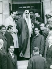Faisal bin Abdulaziz Al Saud being surrounded and welcomed by people and friends.
