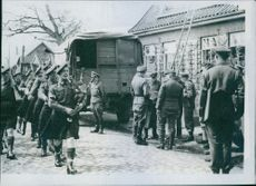 While British and German officers discuss the occupation arrangements in the road, the argyll pipers go swinging by.