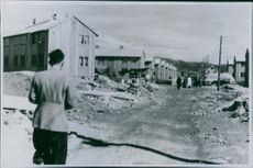 Man standing in street and looking at the debris.