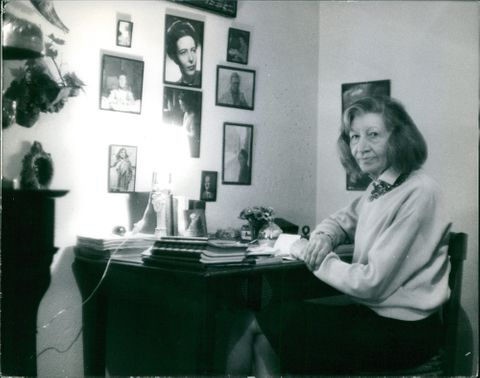 Violette Leduc strike a pose on her desk, looking at the camera with legs crossed, 1964.