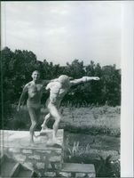 Man holding and posing with a statue.