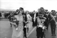 Queen Juliana walking with a bouquet in her hand.