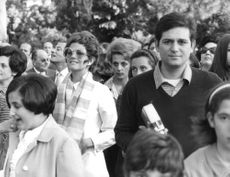 Claudia Cardinale standing in the crowd, wearing a striped muffler around her neck.
