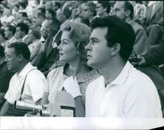 Portrait of Rhonda Fleming watching something beside her a man siting.