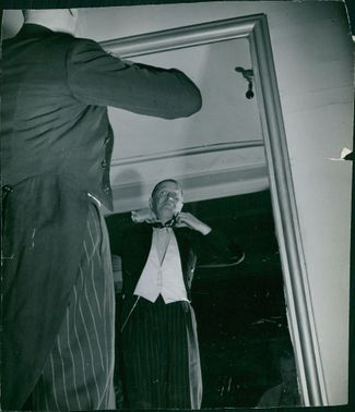 Maurice Auguste Chevalier watching in miror.