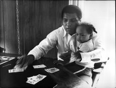 Muhammad Ali shows a short trick for his little daughter.