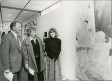 Pehr G. Gyllenhammar standing with his family while looking the painting, 1987.