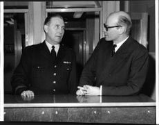 Mayor Gosta Agrenius and Commissioner E. Anling, Kungsholms police chief, at the 'front desk' at the rebuilt guard station.