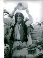 A Yemeni vendor pouring grains from a bucket.  - Nov 1962