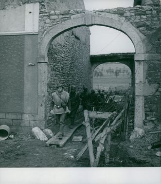 Soldiers passing through the rubble by the road from the ruined buildings damaged by war.