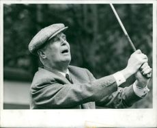 Maurice Chevalier playing golf.
