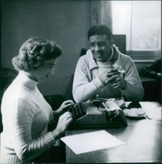 """Man talking to a woman, who's typing on a typewriter.  """"Turpins""""  1954"""