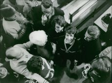 Christine Goitschel looking up with people surrounding her, 1964.