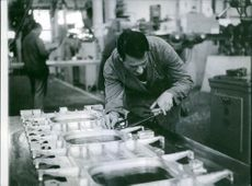 Man working in the workshop and taking measurement.