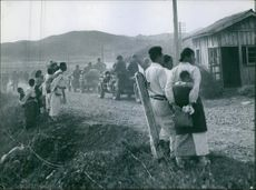 Troops passing by the street in vehicles, people standing and looking at them.1950