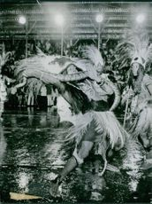 Men wearing traditional clothing and dancing with python.