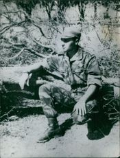 A soldier looking at something, sitting.