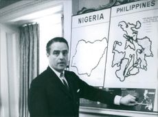 R. Sargent Shriver pointing at the map. 1962.