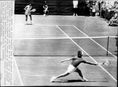 Tennis player Bobby Riggs throws himself behind the ball during a tennis match at Margaret Court.
