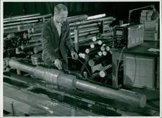A worker working with an ultra light device in a factory.