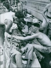 Soldiers holding an injured man during war in France. 1954.