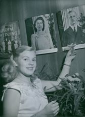 Woman standing and holing glass of drink, showing photo frame on the wall.