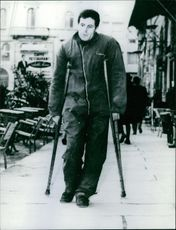 A photo of disabled man walking in the street. May 17, 1968
