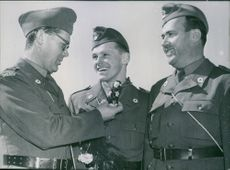 Three soldiers smiling at each other while one of them holds and show a miniature monkey with rifle.