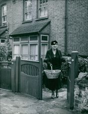 Mrs. Hagborg carrying a basket while stepping out of her house. 1939.