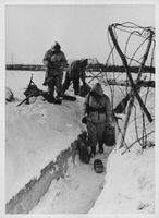 Three armed men making way through the snow.  - 1943
