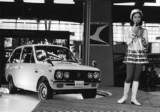 A model standing in front of car.