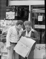 Two men stay at a newsstand in Liverpool to read business reports in a news magazine