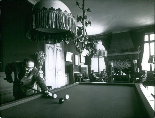 A man smoking a cigarette and playing billiards by himself while the ladies in the background looks on.