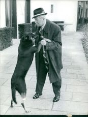 Maurice Auguste Chevalier playing with dog.