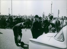 People gathered on the road, policemen holding and taking away a criminal.