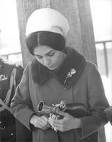Farah Pahlavi holding and looking down at a film camera.