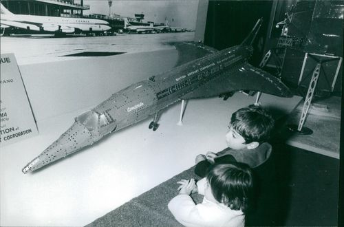 Children looking at airplane model.