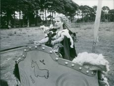 """Carita Järvinen riding a chariot as one of the scenes in the 1967 movie, """"The Viking Queen""""."""