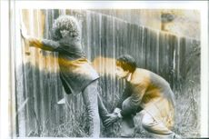 """Mathew Broderick assisting a Heidi Kling to climb on a wall in the scene from the movie, """"Out on a Limb""""."""