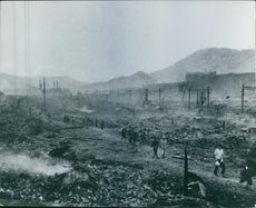 Japanese people walking and looking after the bombardment.