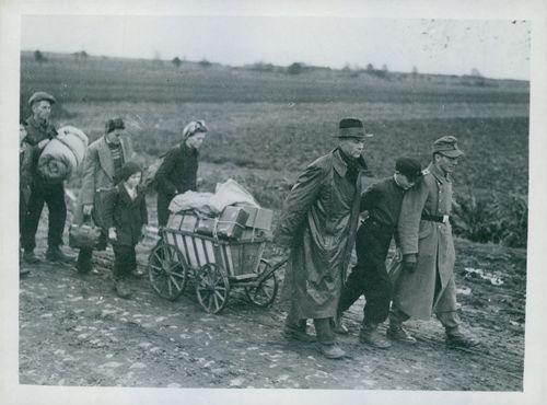 Refugees with their belongings while trekking across the border of the British zone.
