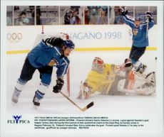Finland's Teemu Selanne picks the puck in the box behind Tre Kronor's goalkeeper Tommy Salo. Finland won the match by 2-1.