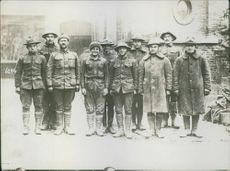Soldiers standing together for a group photograph and smiling.