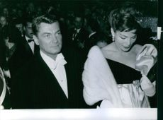 Jean Marais is attending a formal event with a lady.